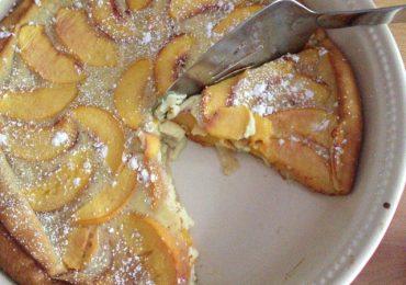 Сладкиш с праскови, направен от пухкав яйчен крем и поръсен с пудра захар – върховно удоволствие